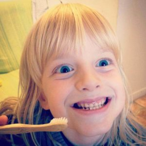 Kid smiling with a toothbrush