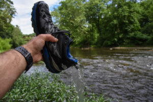 man showing waterproof strength of gore-tex hiking boots
