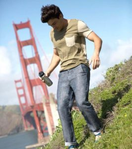 man wearing betabrand travel pants and carrying a water bottle in front of san francisco bay