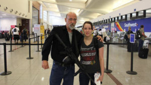 man with a gun and a girl on an airport