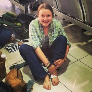 Woman cleaning her foot with wet wipes at an airport