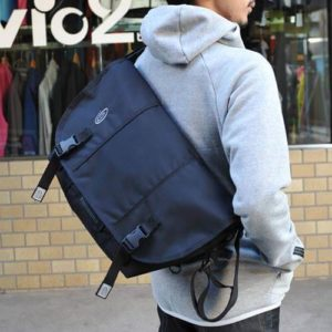 man carrying timbuk2 classic messenger bag infront of a clothing store