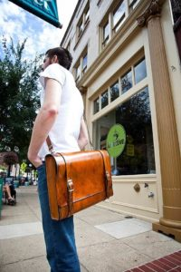 A man carrying leather messenger bag infront of a cafe