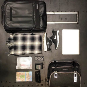 A well organized suitcase with packed items lying beside it