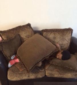 A sleeping man using cusions as blanket