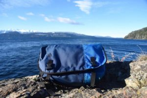 A blue Timbuk2 classic messenger bag in front of a lake
