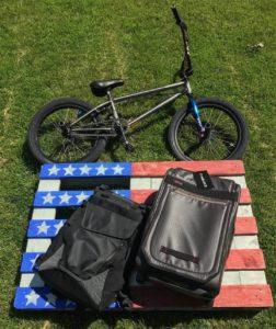 suitcase lying on american flag beside a mountain bike