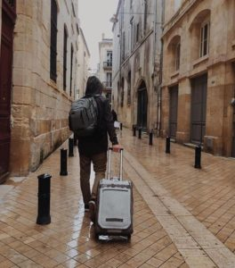man carrying a suitcase on urban street