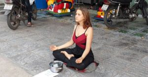 western Woman begging for money in vietnam doing yoga